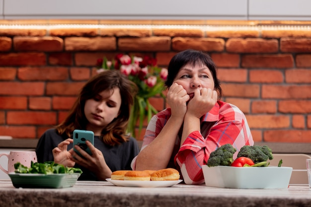 Teenager is sitting with the phone next to hir grandmother and does not pay attention to her