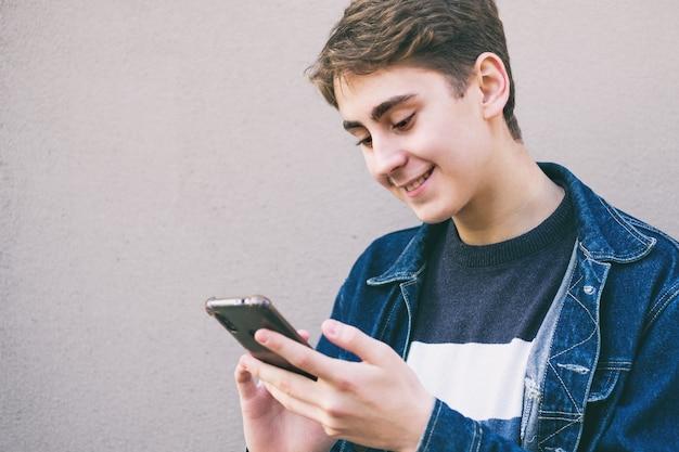 Подросток использует телефон и улыбается - счастливый подросток, держащий телефон в руке