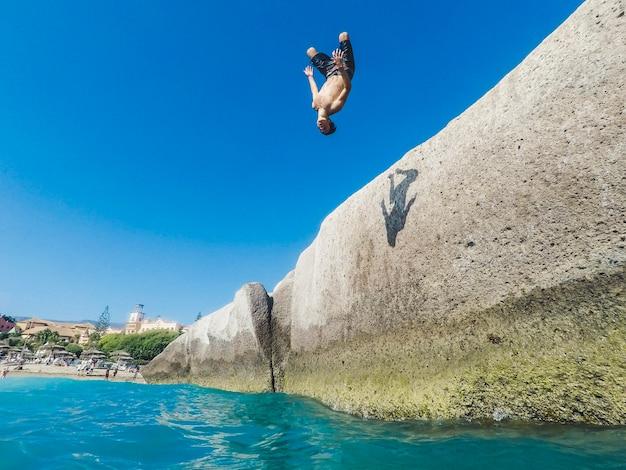 Подросток прыгает в море по скалам, и некоторые люди смотрят на него - очень опасное занятие, и парень делает сальто назад и больше вольным стилем