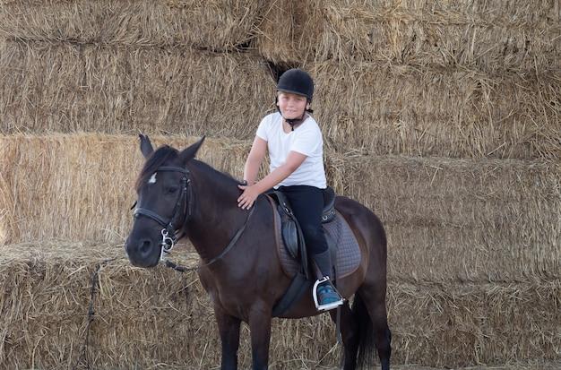 乗馬学校で乗ることを学ぶティーンエイジャー