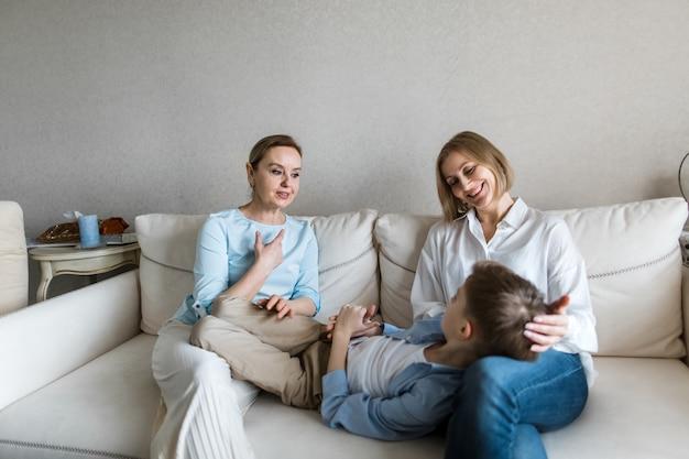 Подросток лежит на коленях у взрослой женщины, и все общаются
