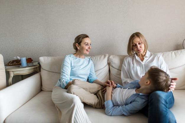 Подросток лежит на коленях у взрослой женщины и все общаются