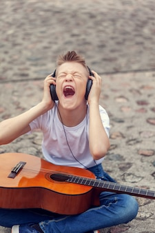 Teenager listening to music on headphones and screaming song. young man sitting with a guitar on the street.