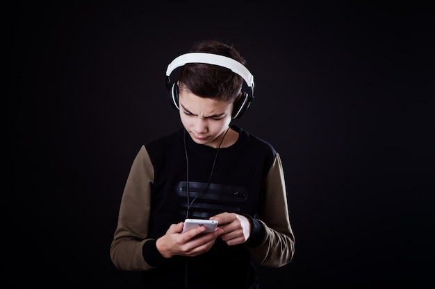 Teenager listens to music on a black background