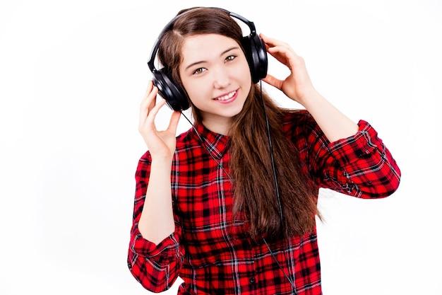 ティーンエイジャーは白い壁のスタジオで音楽を聴きます