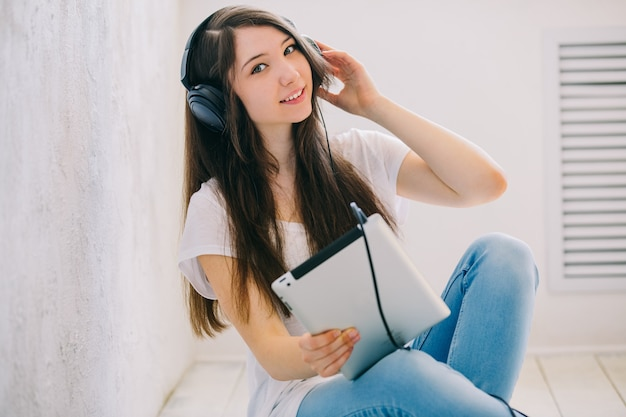 Подросток слушает музыку, сидя на полу