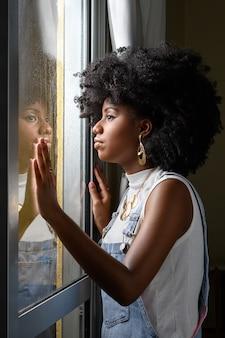 10代の若者は、パンデミック・コビッドの中で雨に濡れたガラスを押し下げて窓の外を眺めます19