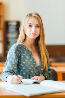 Teenager making notes and looking at camera