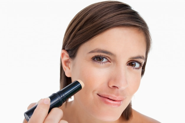 Teenager making-up while applying foundation with brush