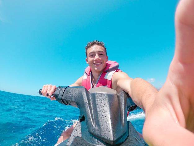 Человек-подросток наслаждается летом на гидроцикле посреди моря, весело гоняясь в одиночестве и изолированном.