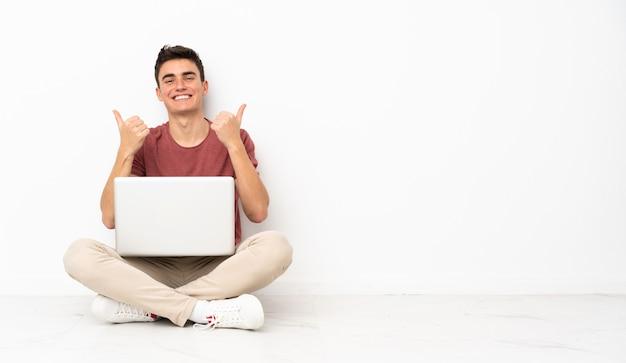 제스처와 엄지 손가락 자신의 노트북과 함께 바닥에 앉아 십 대 남자