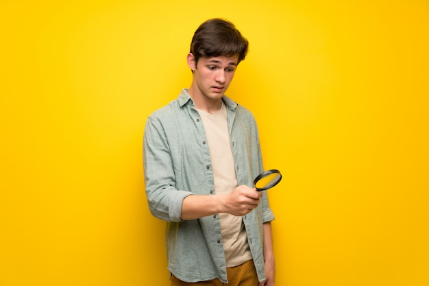 Teenager man over yellow wall holding a magnifying glass