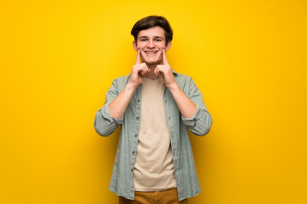 Teenager man over yellow wall smiling with a happy and pleasant expression