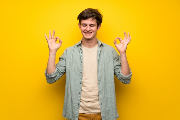 Teenager man over yellow wall in zen pose