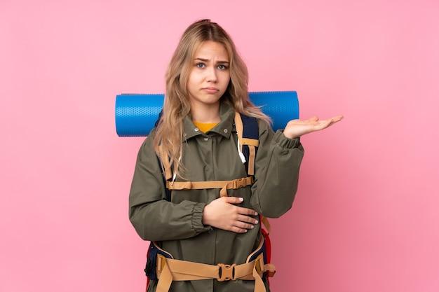 Девушка-подросток-альпинист с большим рюкзаком изолирована на розовом, недовольна тем, что чего-то не понимает