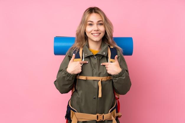 Девушка-подросток-альпинист с большим рюкзаком изолирована на розовом с удивленным выражением лица