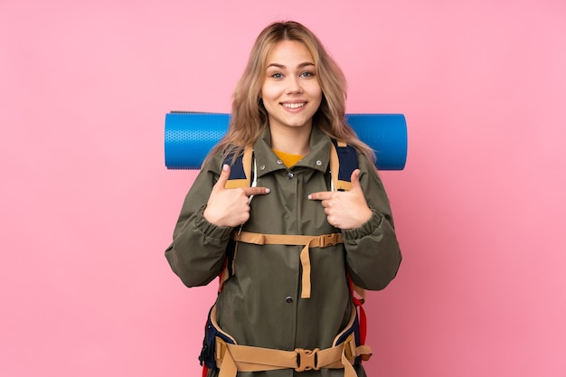 Teenager mountaineer girl with a big backpack isolated on pink with surprise facial expression