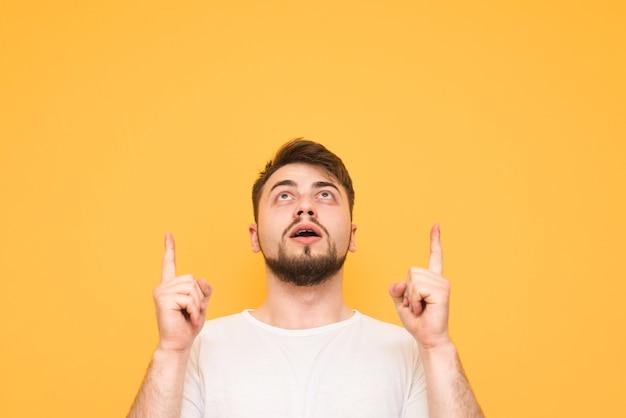 Подросток на желтом, глядя вверх и показывая пальцами на пустом месте