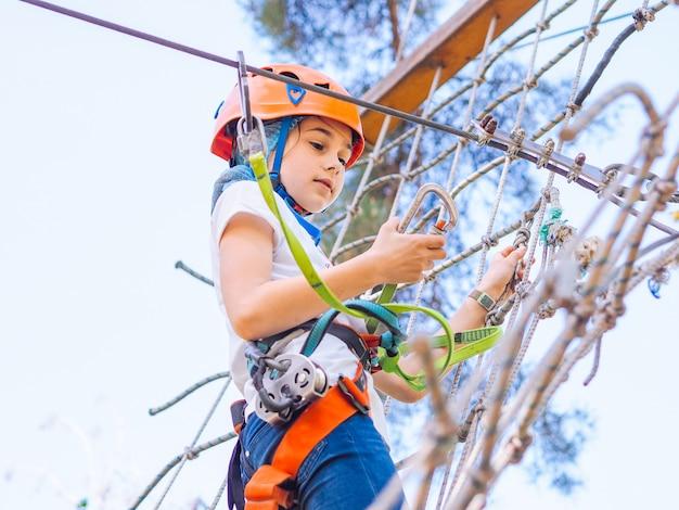 Teenager in orange helmet climbing in trees on forest adventure park.