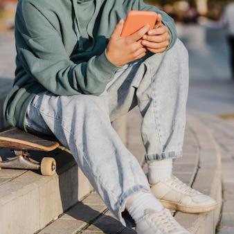 Подросток на открытом воздухе держит смартфон, сидя на скейтборде