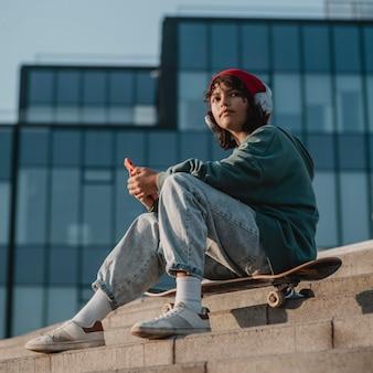Подросток на открытом воздухе слушает музыку в наушниках во время использования смартфона