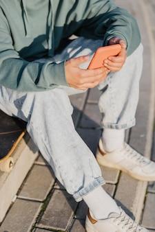 スケートボードに座っている間スマートフォンを持って外のティーンエイジャー