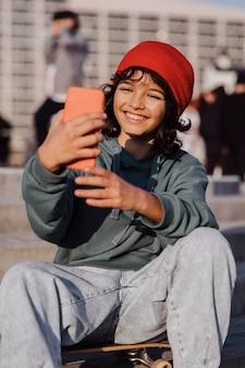 Подросток снаружи сидит на скейтборде и делает селфи