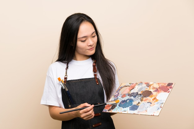 Teenager painter asian girl over isolated wall