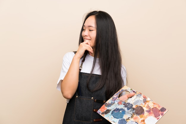 Teenager painter asian girl thinking an idea and looking side