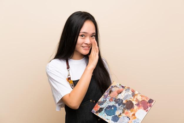 Teenager painter asian girl whispering something