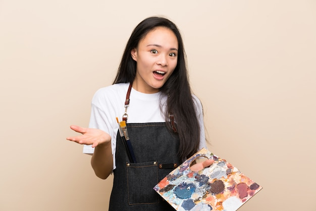 Teenager painter asian girl with shocked facial expression