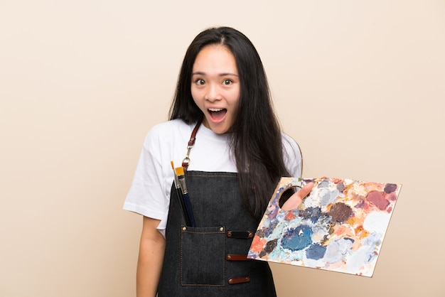 Teenager painter asian girl with surprise and shocked facial expression