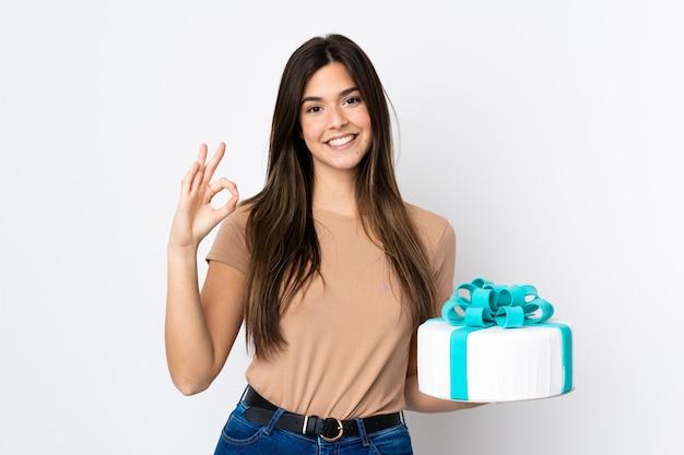 指でokの標識を示す分離の白い背景の上に大きなケーキを保持しているティーンエイジャーのパティシエ