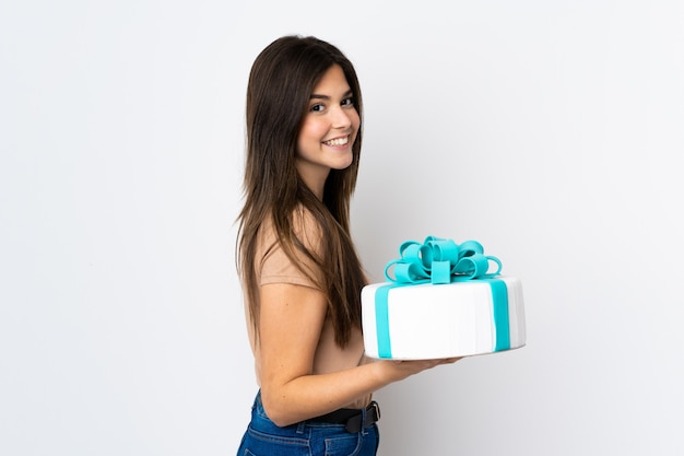 Подросток кондитер держит большой торт над изолированной белой стене, много улыбается