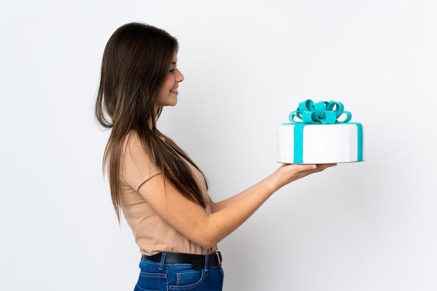 幸せな表情で孤立した白い壁に大きなケーキを持って10代のパティシエ
