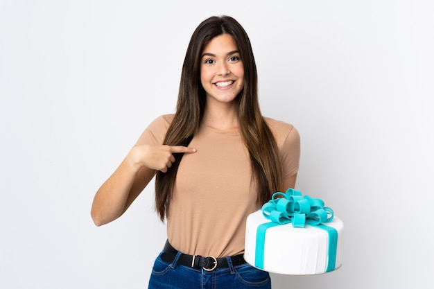 Teenager pastry chef holding a big cake over isolated white background with surprise facial expression