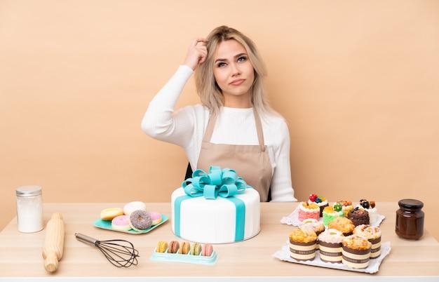 10代のペストリーシェフ、テーブルに大きなケーキがあり、疑いの表情を混乱させる