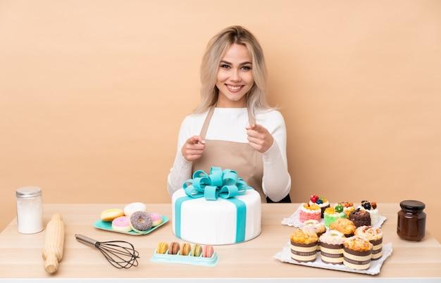 テーブルに大きなケーキを持つ10代のパティシエが指を指す