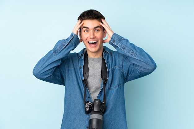 Teenager photographer man isolated on blue with surprise facial expression