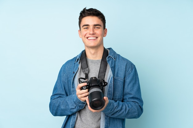 Teenager photographer man isolated on blue