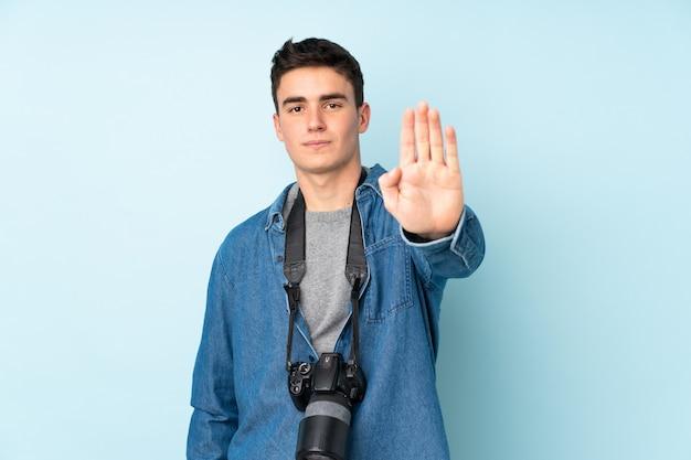 그녀의 손으로 중지 제스처를 만드는 파란색 배경에 고립 된 십대 사진 작가 남자