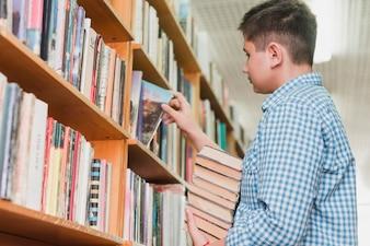 Teenager picking books from shelf