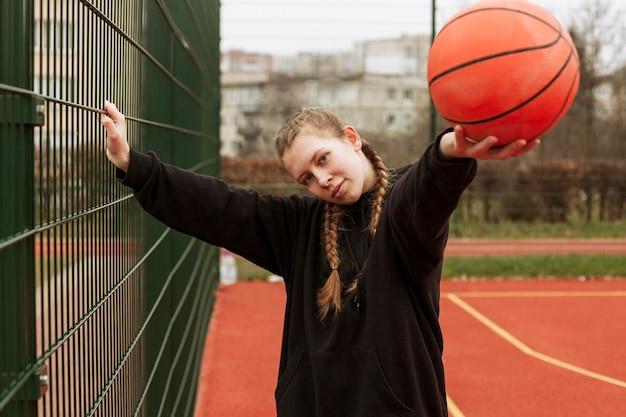Подросток играет в баскетбол на открытом воздухе
