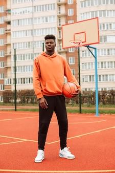 Adolescente che gioca a basket all'aperto