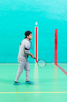 Teenager playing frontenis with a racket