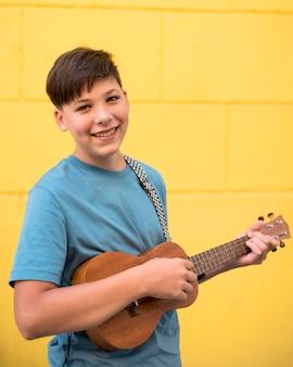 Подросток играет на укулеле
