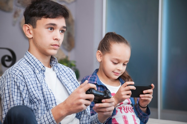Teenager playing video games near sister