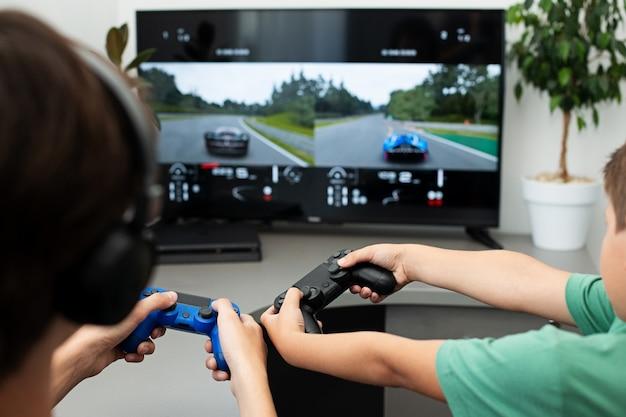 ティーンエイジャーは、ヘッドフォンとジョイスティックでコンピューターゲームをプレイします。