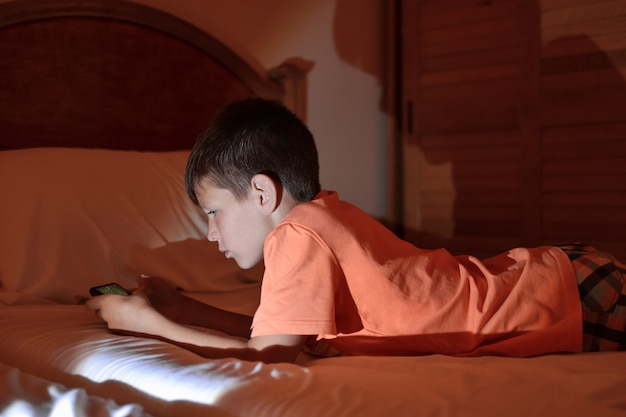 The teenager plays a game on a mobile phone while relaxing in a hotel room