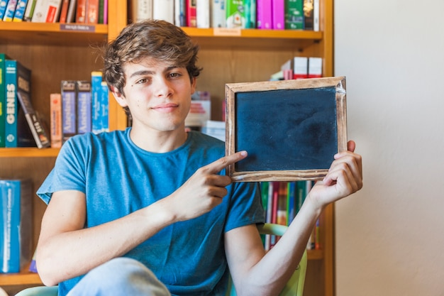 Teenager pointing at small chalkboard